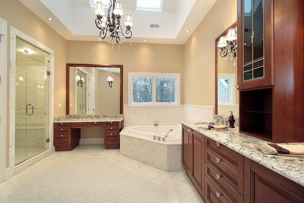 Large wooden vanities flank a corner tub that's fixed underneath the glazed window. It is illuminated by a gorgeous chandelier along with skylights fitted on the tray ceiling.