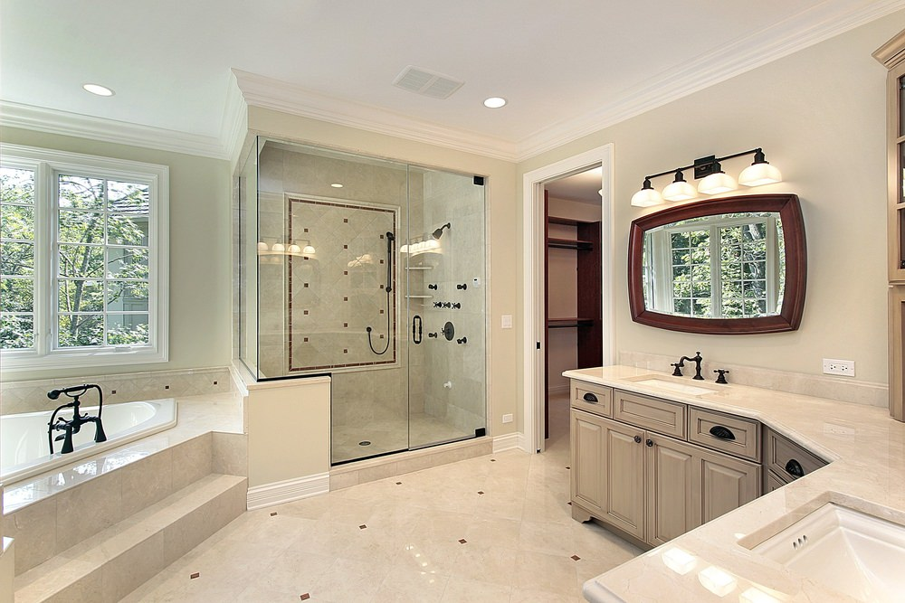 A drop-in tub sits next to the walk-in shower that's accented with wrought iron fixtures. It is accompanied by a curved vanity with dual sink and wooden framed mirror.