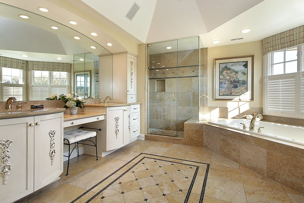 Natural light streams in through the framed windows that are covered in white shutters and striped roman shade. This master bathroom boasts a gorgeous artwork and a walk-in shower situated in between the drop-in tub and dual sink vanity.