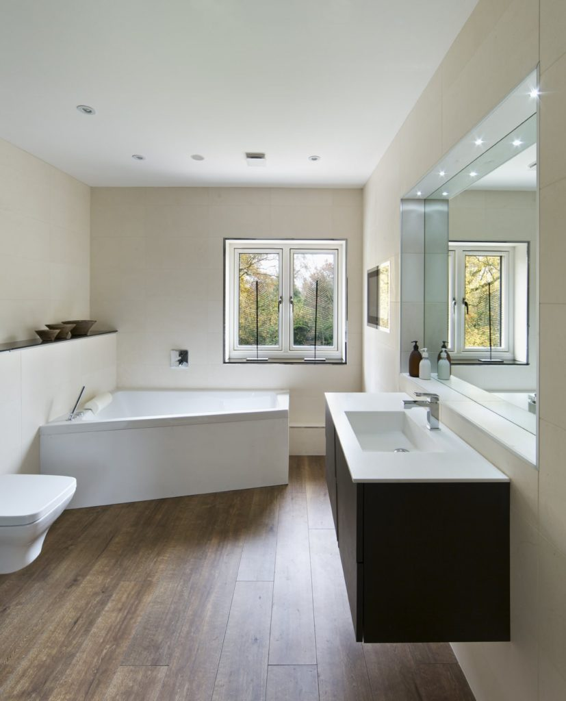 A black floating sink vanity provides a striking contrast to the white corner tub and toilet over the natural hardwood flooring. This master bathroom showcases a glazed window and an inset wall fitted with a frameless mirror that's illuminated by recessed lights.