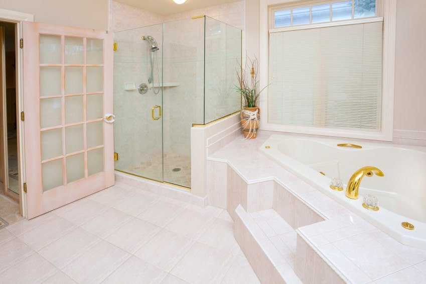 A glazed door opens to this bright master bathroom with a walk-in shower and a corner tub accented with gold fixtures. It has cream tiled flooring and a picture window covered in white roller blinds.