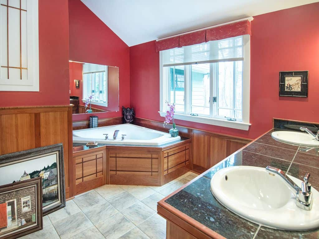 A dual sink vanity faces the corner tub that's clad in wooden panels blending in with the wainscoting. This master bathroom is decorated with gorgeous artworks and red valances covering the white framed windows.
