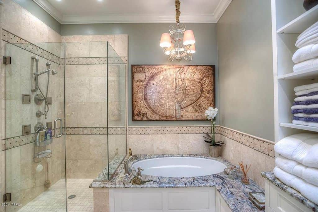 A chrome chandelier illuminates this master bathroom offering a walk-in shower and a drop-in tub integrated with a built-in bench. There's an interesting artwork on top mounted on the gray wall.