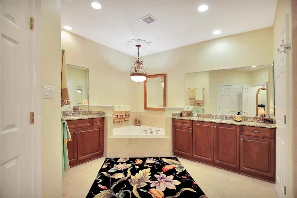 A lovely pendant light hangs over the corner tub flanked by wooden vanities with granite countertops. It is accompanied by a black floral rug that lays on the beige tiled flooring.