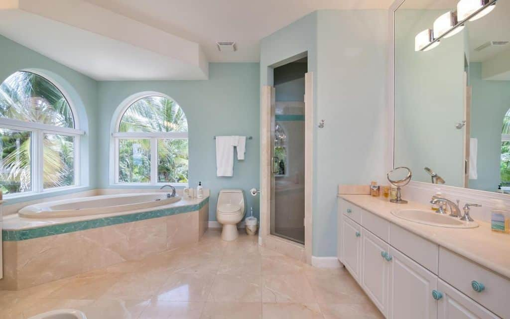 Charming master bathroom with white vanity, walk-in shower and a corner tub by the arched windows. It is clad in beige marble tiles with a blue accent complementing the walls and knobs.