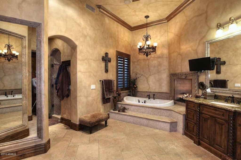 A brick fireplace faces the corner tub that's illuminated by a vintage chandelier. It is accompanied by a wooden vanity and a cushioned stool over limestone flooring.