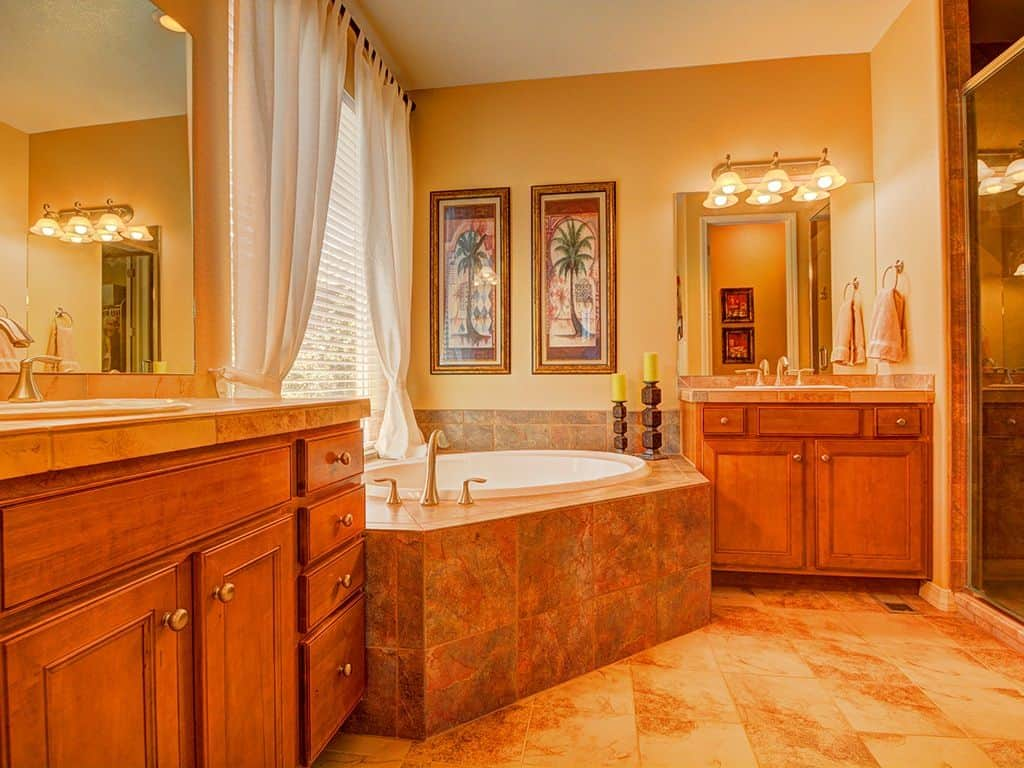 Warm master bathroom designed with tree artworks that hung above the soaking bathtub with chrome fixtures. It is situated in between wooden vanities and frameless mirrors.