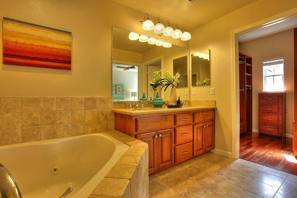 A corner tub sits beside the wooden vanity with a frameless mirror lighted by glass dome sconces. This room is decorated with a warm painting mounted on the beige wall.
