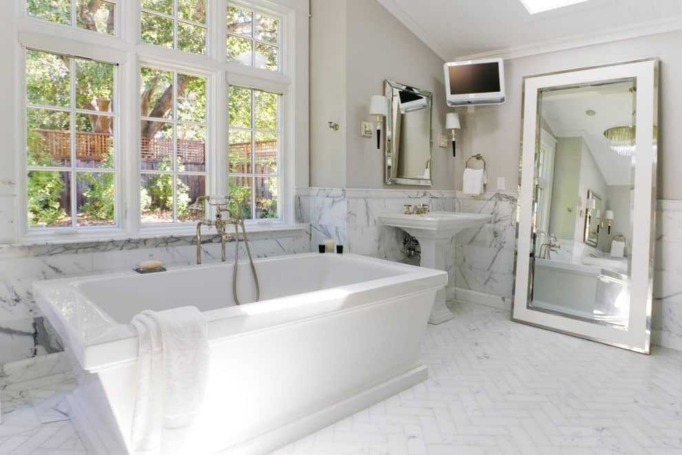 Airy primary bathroom offers a wall mount TV and a beveled mirror that hung above a pedestal sink. It includes a deep soaking tub and a full-length mirror creating a larger visual space in the room.