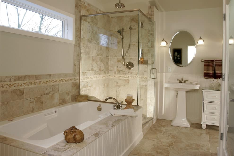 Glass sconces flank an oval mirror that's fixed above a pedestal sink. This primary bathroom boasts a walk-in shower and a deep soaking tub framed in white beadboard.