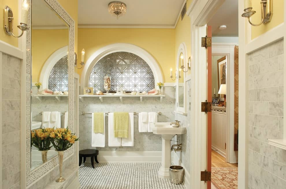 Brick marble tiles dominate the yellow walls in this primary bathroom with a semi-circular window and a pedestal sink paired with an arched medicine cabinet. There's a large mirror on the side accented with a sleek flower vase.
