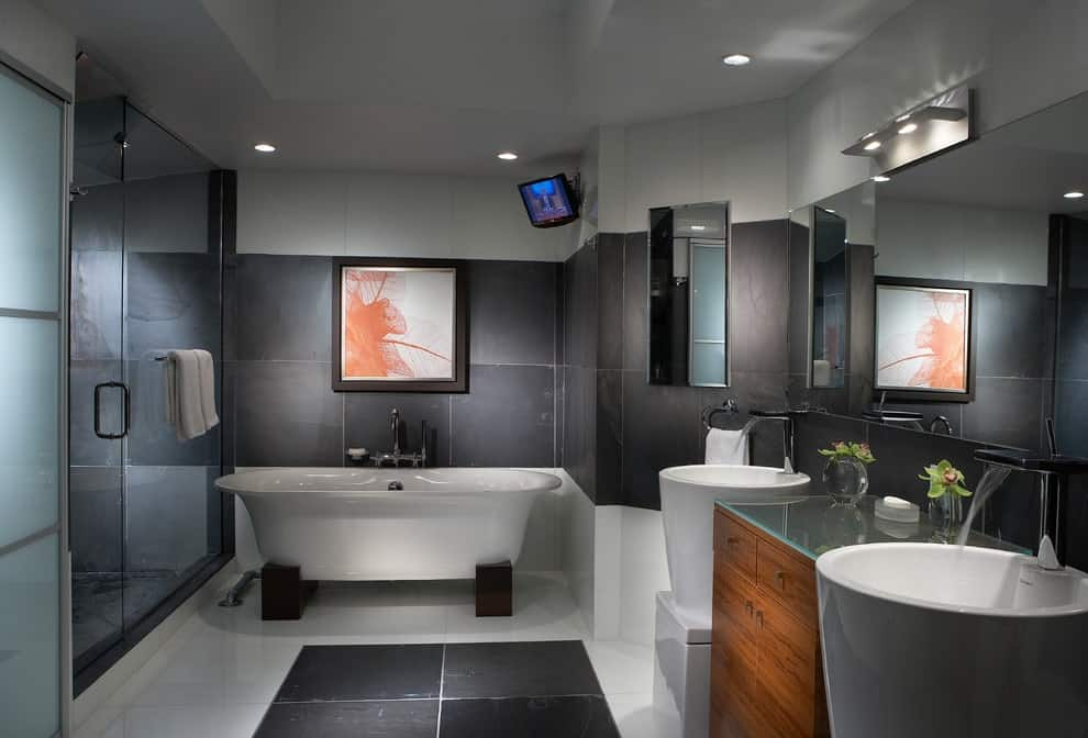 A wooden cabinet sits in between stylish his and her pedestal sinks under a frameless mirror. This primary bathroom features a wall mount TV and a black framed artwork that hung above a freestanding tub.