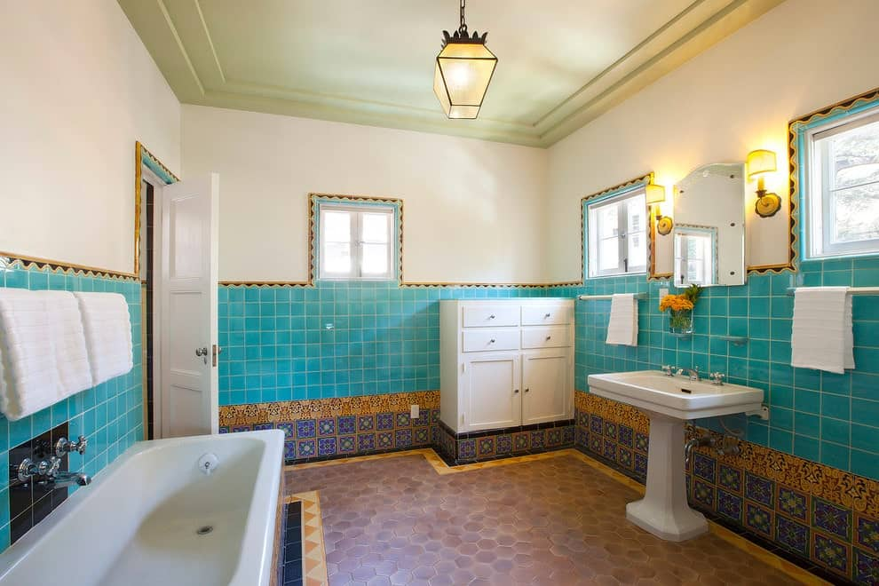 Warm sconces and a glass pendant light illuminate this master bathroom showcasing a deep soaking tub and a white cabinet facing the pedestal sink. It has hex tile flooring and beige walls dominated by green and decorative tiles.