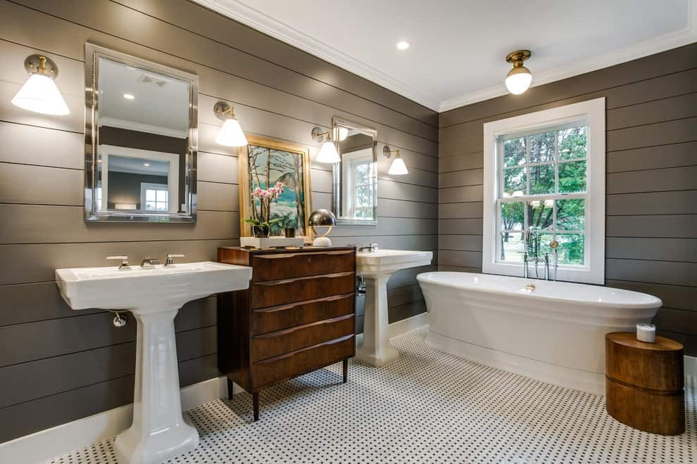 Fresh master bathroom illuminated by a glass pendant light along with matching sconces mounted on the gray shiplap wall. It has a soaking bathtub and a wooden dresser flanked by his and her pedestal sinks.