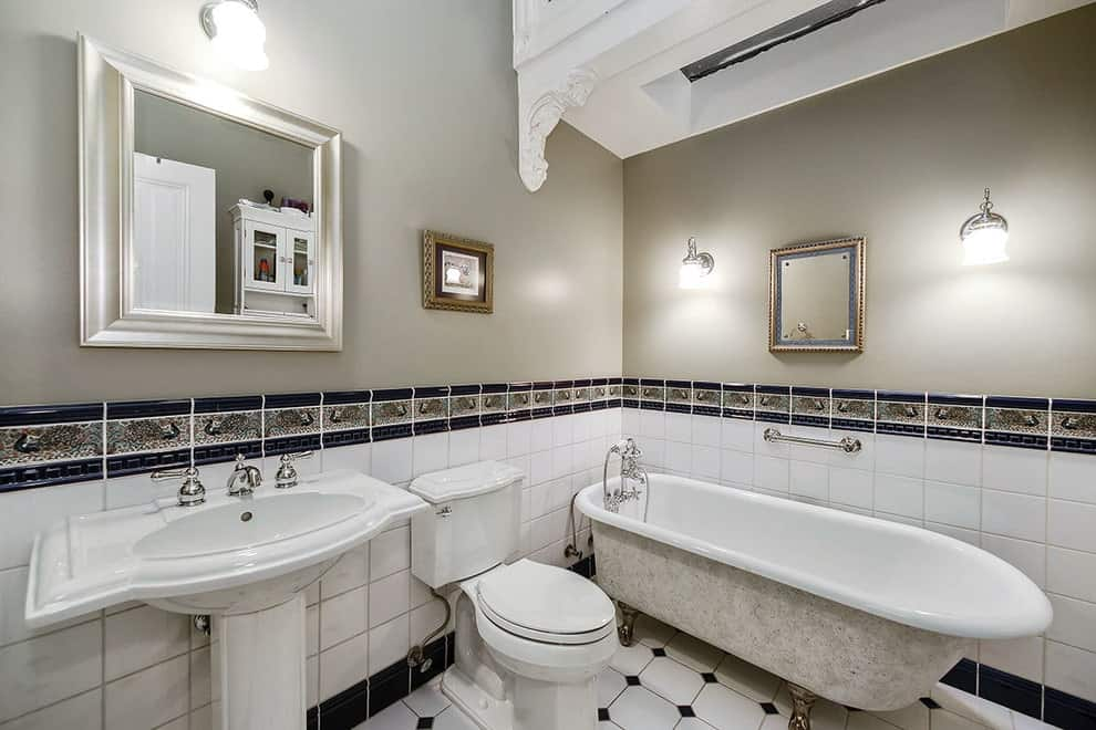 This primary bathroom is decorated with a framed artwork and mirrors lighted by chrome sconces. It has a pedestal sink and toilet along with a clawfoot tub over white tiled flooring.