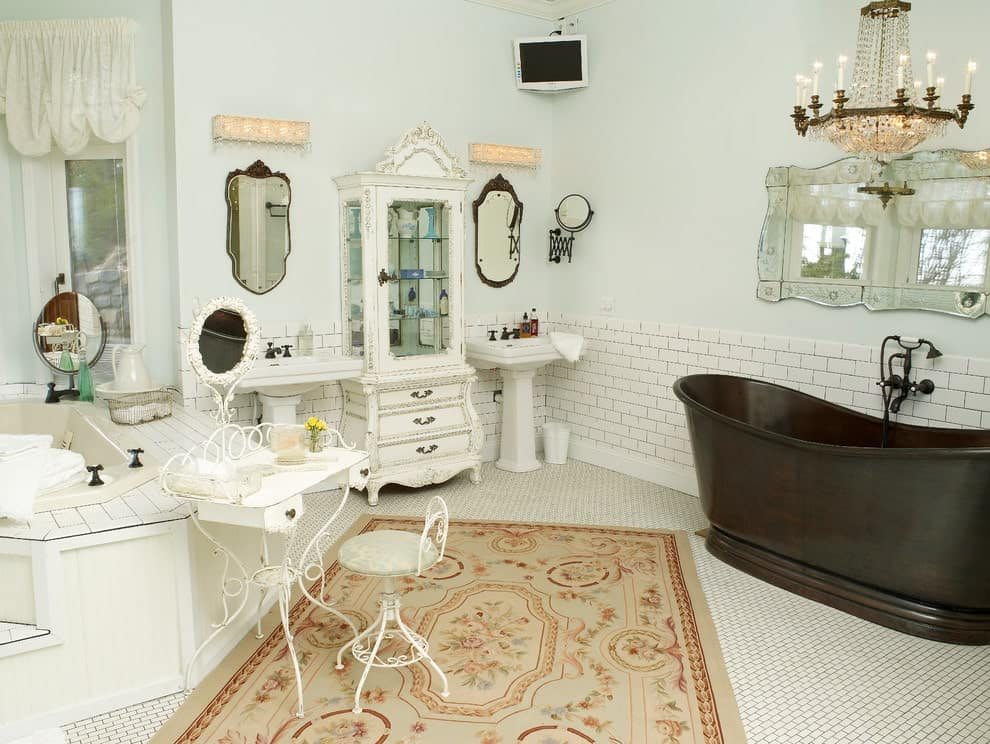 A gorgeous candle chandelier illuminates the bronze bathtub against the white brick lower wall. It is contrasted by a charming cabinet flanked by pedestal sinks along with a white metal vanity over a floral area rug.