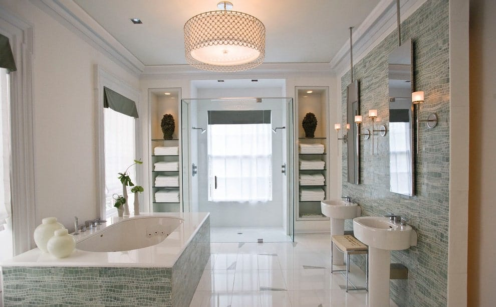 Green tiled accent wall matches the bathtub surround by the glazed windows dressed in white sheer curtains. This primary bathroom boasts a pair of pedestal sinks and a walk-in shower with his and her shower heads flanked by inset shelves.