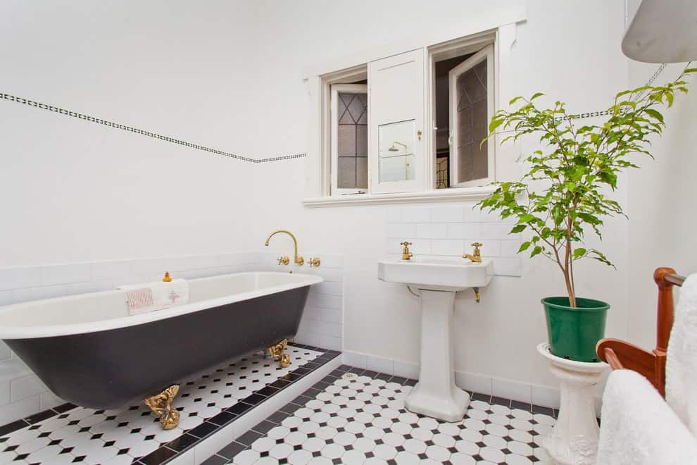 A large potted plant creates a refreshing ambiance in this primary bathroom showcasing a black clawfoot tub and a porcelain pedestal sink accented with gold fixtures.