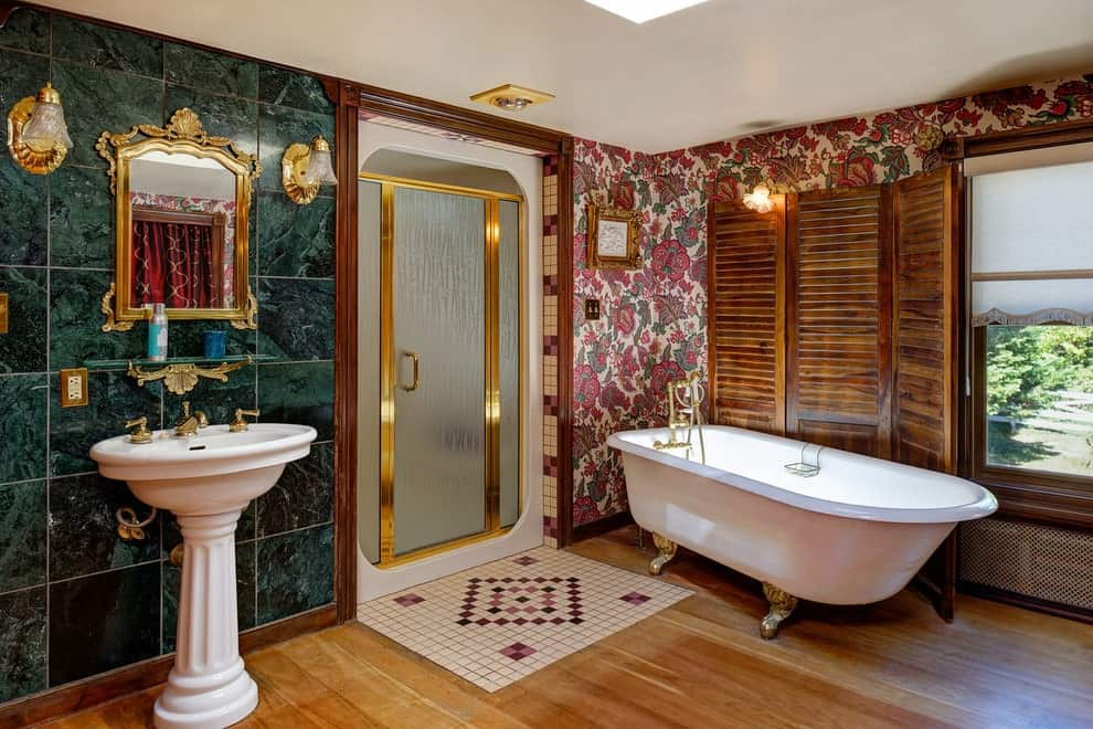 A louvered three-panel screen sets a cozy backdrop to the clawfoot tub over the hardwood flooring. It is accompanied by a walk-in shower and a pedestal sink accented with brass fixtures that complement the classy mirror and wall sconces.