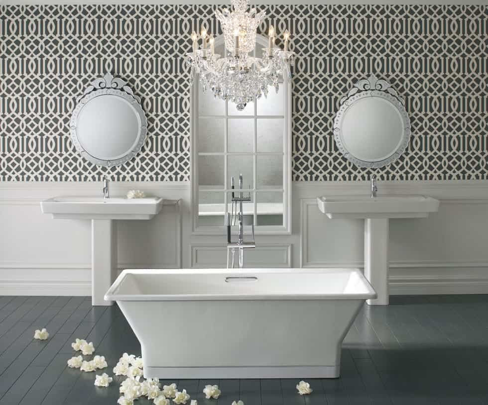 Deluxe primary bathroom offers a freestanding tub illuminated by a fancy crystal chandelier along with his and her pedestal sinks that are paired with gorgeous mirrors against the patterned wallpaper.