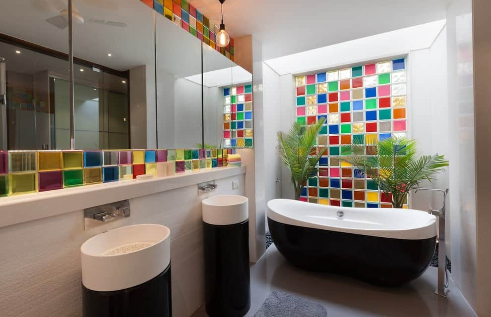 Multi-colored backsplash tiles bring a pop of colors in this primary bathroom with frameless mirrors and sleek pedestal sinks complementing the stylish bathtub that's accented with tropical plants.