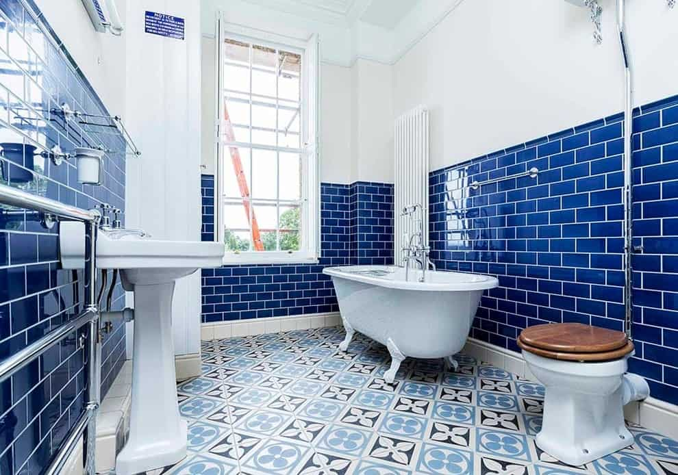 Bright primary bathroom offers a clawfoot tub and a toilet facing the pedestal sink against the blue subway tiles. It has decorative tile flooring and a white framed window allowing natural light in.