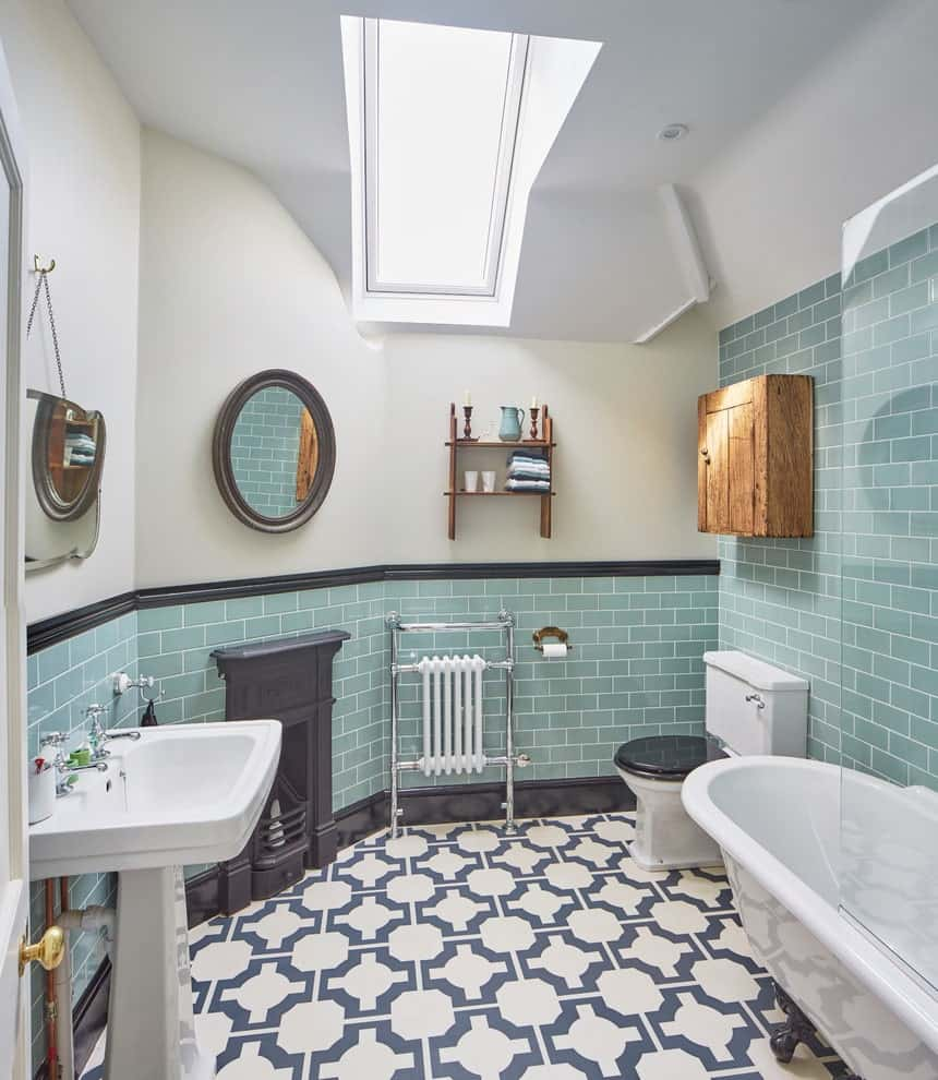 Patterned flooring adds a striking accent in this primary bathroom showcasing a pedestal sink and a toilet next to the clawfoot tub. It includes a floating cabinet and shelf along with mirrors mounted above the green brick lower wall.