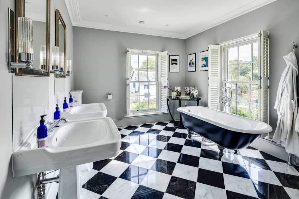 The traditional primary bathroom features his and her pedestal sinks and a black clawfoot tub with a round high gloss table on the side. It has checkered flooring and large framed windows covered in white shutters.