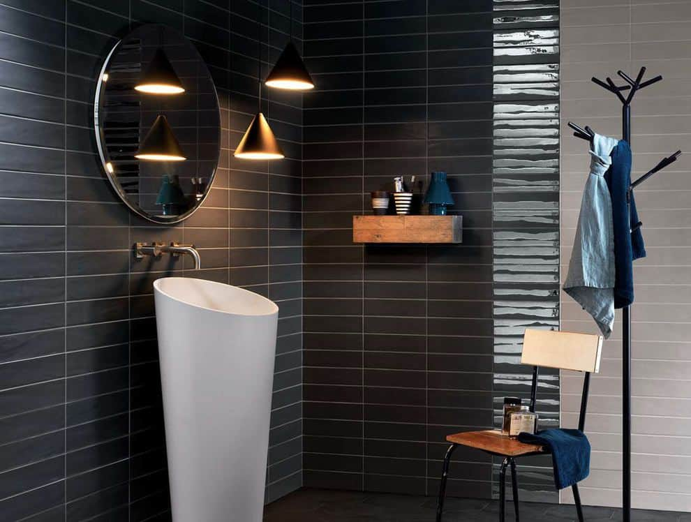 A sleek pedestal sink stands out against the black tiled walls mounted with a rustic floating shelf and a round mirror. It is accompanied by dome pendant lights and a metal chair next to the wrought iron rack.