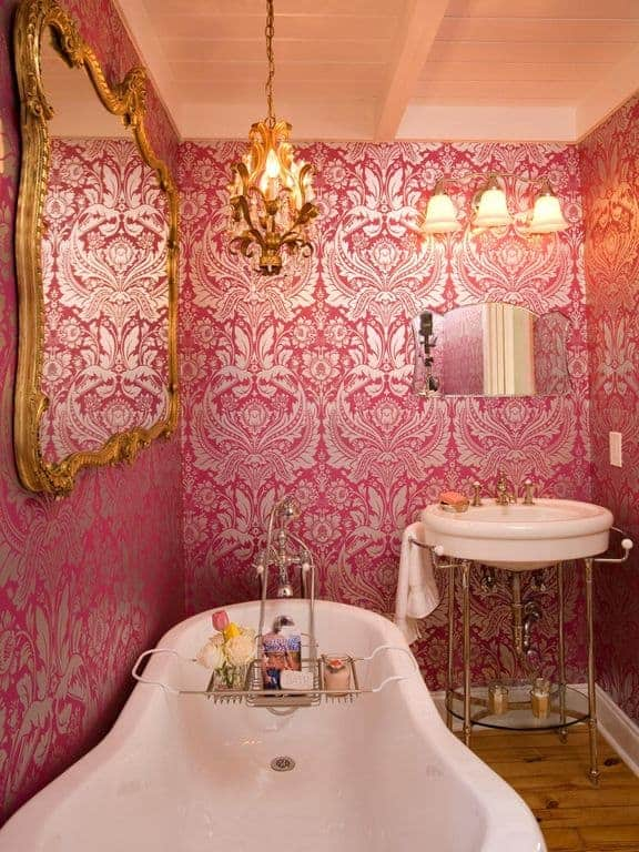 Clad in pink floral wallpaper, this primary bathroom offers a round pedestal sink and a deep soaking tub that's topped with a stainless steel caddy. It includes elegant mirrors and a gold chandelier that hung from the beamed ceiling.
