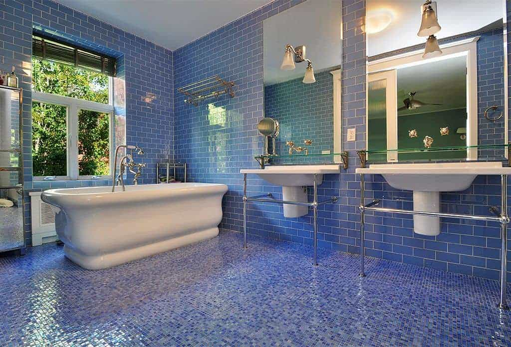 Blue master bathroom with stunning mosaic tile flooring and a glazed window covered in black roller blinds. It includes a freestanding tub and a pair of pedestal sinks with chrome bases.