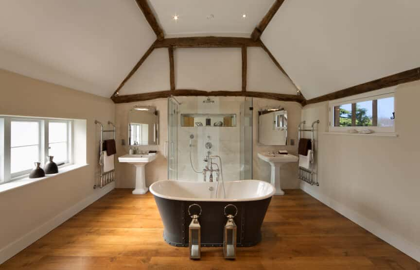 A freestanding tub sits in front of the walk-in shower flanked by pedestal sinks and frameless mirrors. This master bathroom has rich hardwood flooring and a vaulted ceiling framed with rustic wood beams.