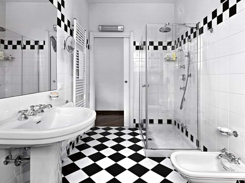 Bordered tiles and checkered flooring add a striking accent in this white master bathroom with pedestal sinks and a walk-in shower that's fitted with chrome fixtures.