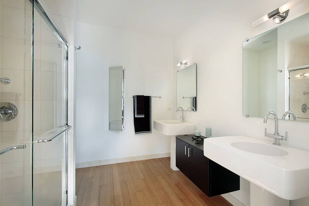 This master bathroom features a walk-in shower and a black floating cabinet contrasted by sleek pedestal sinks under frameless mirrors. It is illuminated by linear glass sconces mounted on the white wall.