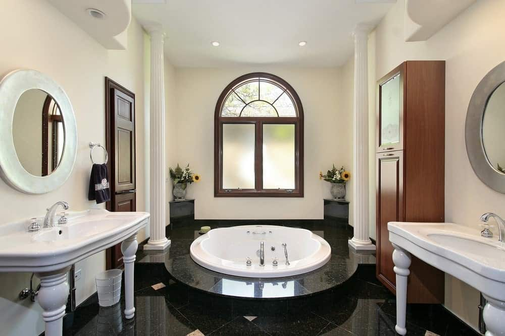 An arched window is fixed above a drop in bathtub lined with white columns. It is accompanied by a wooden cabinet and pedestal sinks that are paired with round mirrors.