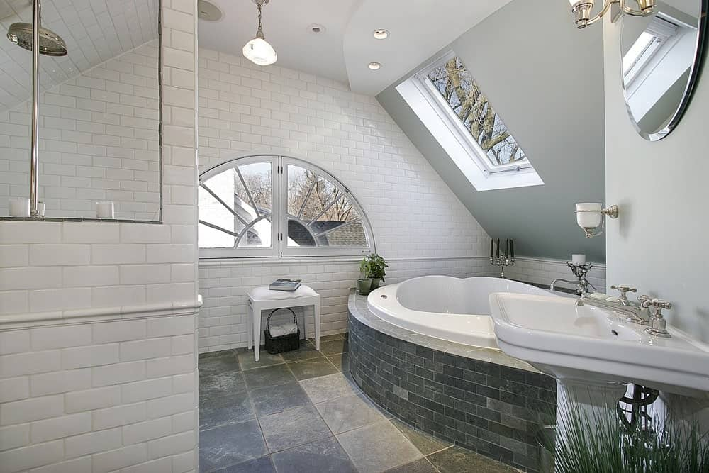 White subway tiles dominate the gray walls that are fitted with a skylight window. This primary bathroom showcases a pedestal sink and a deep soaking tub clad in gray bricks.