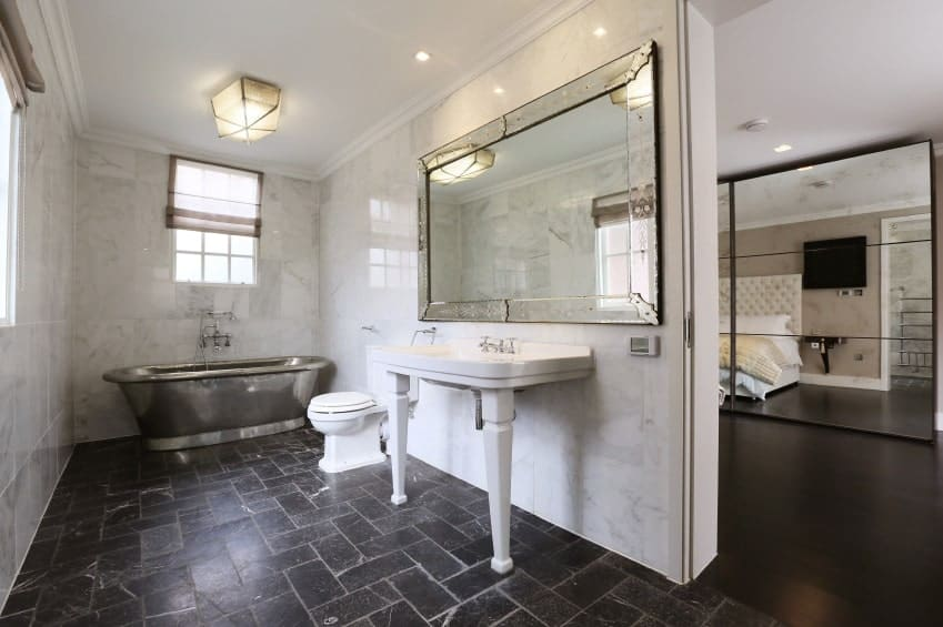 A chrome freestanding tub faces the toilet and pedestal sink with a large framed mirror on top. It is surrounded by marble tiled walls and glazed windows covered in translucent roman shades.