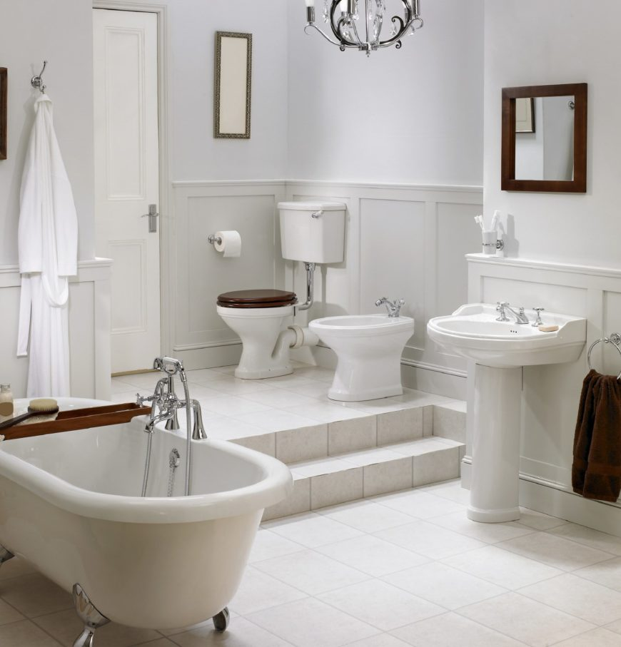 White primary bathroom with wainscoted lower walls and tiled flooring that extends to the steps leading to the toilet area. It includes a pedestal sink and a clawfoot tub lined with a bamboo tray.