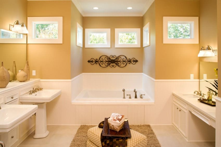 A patterned ottoman sits in between the pedestal sink and vanity lighted by glass sconces. There's a drop-in tub across and an ornate wrought iron decor that adds a nice accent to the beige walls.