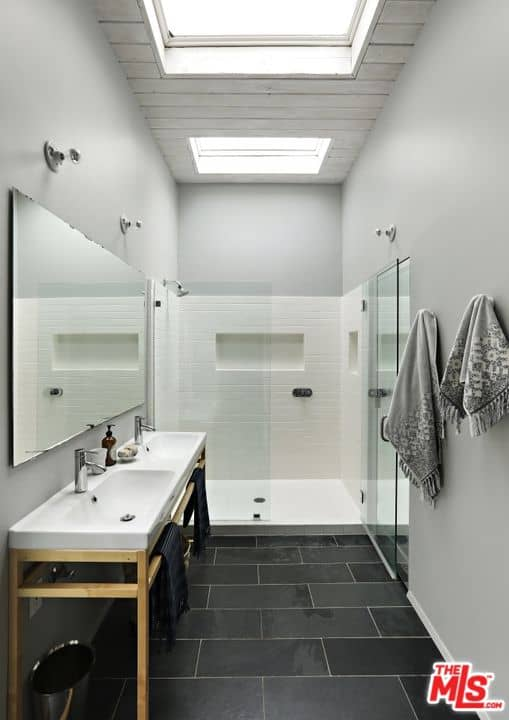 A narrow primary bathroom with black tiled flooring and a shiplap ceiling fitted with skylights. It includes a walk-in shower and a light wood pedestal with dual sink under a frameless mirror.