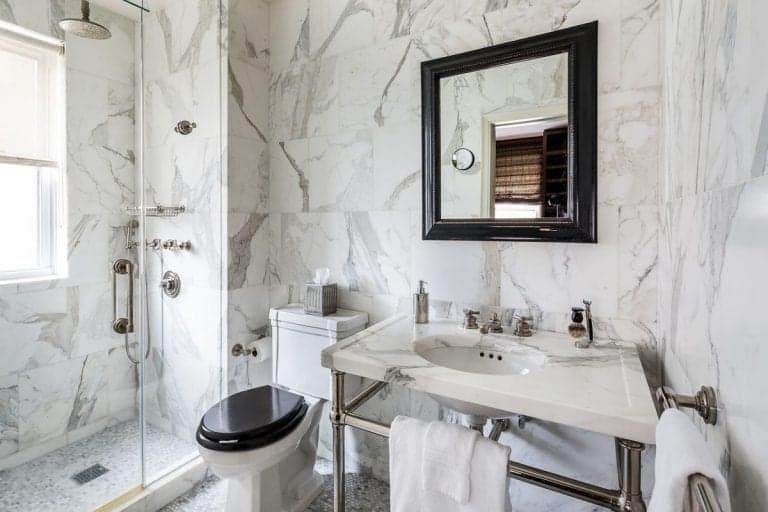 A black framed mirror hangs above a chrome pedestal sink with a marble counter matching with the tiled walls. It is accompanied by a toilet and a walk-in shower with stainless steel fixtures.
