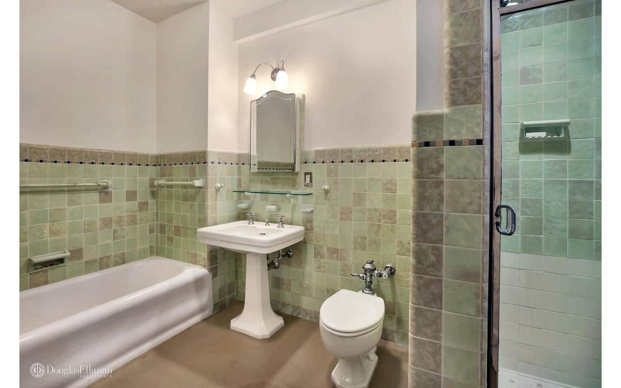 This master bathroom boasts a bathtub and toilet along with a pedestal sink that's paired with a glass floating shelf and mirrored medicine cabinet lighted by chrome sconces.