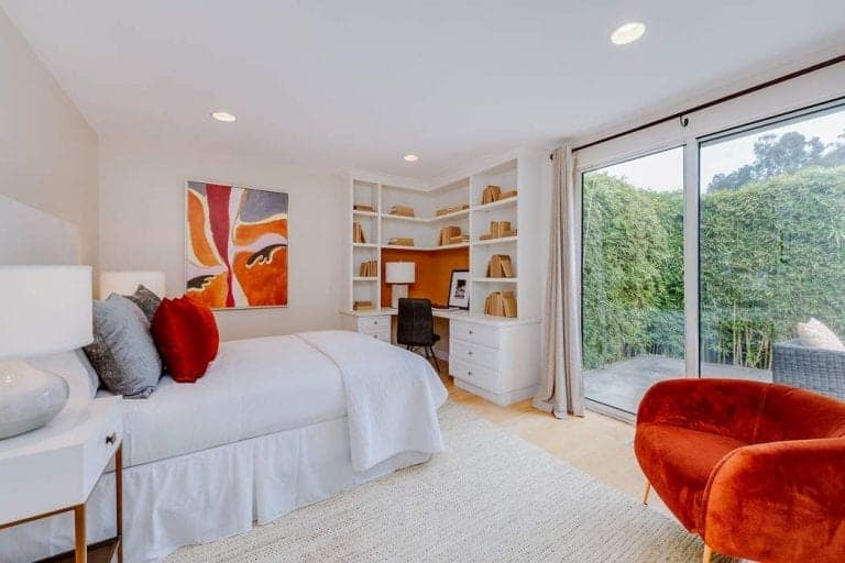 White primary bedroom featuring a white bed lighted by white table lamps on both sides. The room also offers a built-in desk with shelving and drawers.