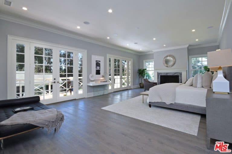 A spacious primary bedroom featuring a regular white ceiling, gray walls and hardwood floors. The room offers a fireplace with sitting chairs, a modish bed set lighted by stylish table lamps on both sides, on top of gray bedside tables, along with a built-in desk near the doorways.