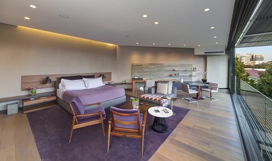 Large primary bedroom featuring a regular white ceiling with recessed ceiling lights and hardwood flooring topped by a purple area rug where the bed is set. On the side, the room offers a coffee table set and a built-in study desk.