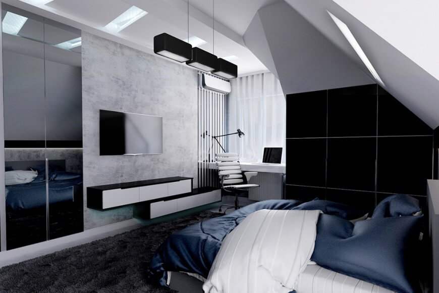 Modern primary bedroom featuring carpeted flooring and a custom white ceiling, together with black and gray walls. The room offers a stylish bed with a flat-screen TV set in front. There's a built-in study desk on the side of the room as well.