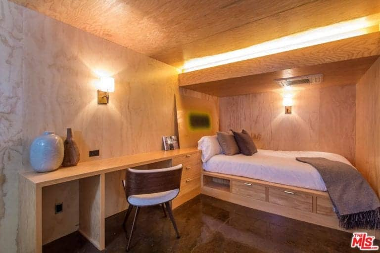 Brown primary bedroom featuring a stylish bed setup and a built-in study desk with drawers, lighted by wall lights.