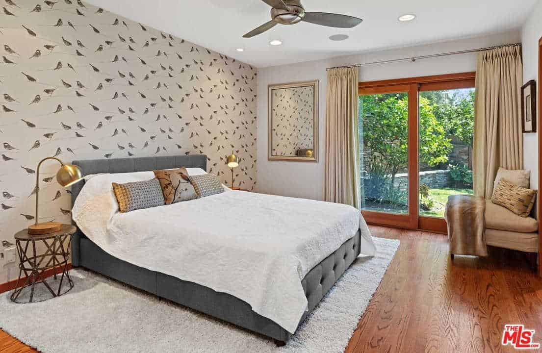 A bird patterned wallpaper sets a serene backdrop to the gray tufted bed flanked by metal nightstands and brass desk lamps. It is accompanied by a wall mirror and a beige seat under the black framed artwork.