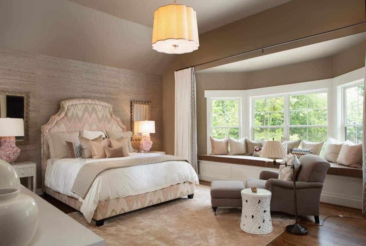 The charming master bedroom showcases a lovely patterned bed and a window seat nook completed with brown cushion and neutral pillows. It includes gorgeous table lamps and a gray lounge chair paired with a white side table.