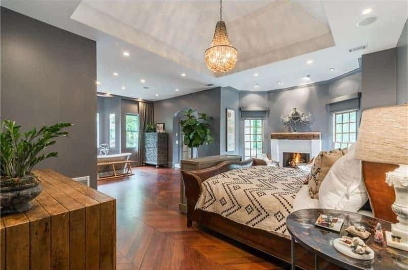 This primary bedroom offers a white fireplace flanked by glazed windows along with a wooden bed over rich hardwood flooring that's arranged in a chevron pattern. It is illuminated by recessed lights and a warm chandelier that hung from the tray ceiling.